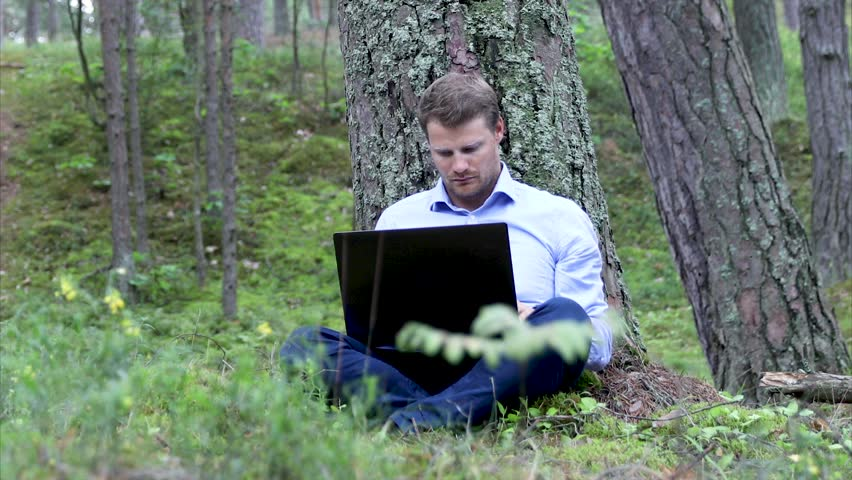 Freelancer working on laptop under the tree in the woods   Shutterstock HD Video #1013594114