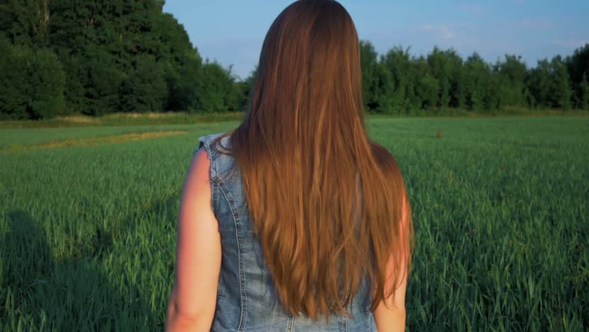 Beautiful young girl with straight long hair develops in the wind, standing in the field at sunset | Shutterstock HD Video #1013598164