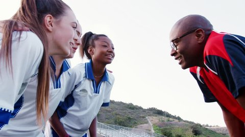 Female High School Sports Team And Coach Having Team Talk