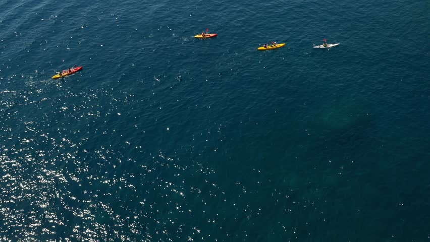 Long shot aerial shot of a large group of sea kayakers following their leader in the open sea