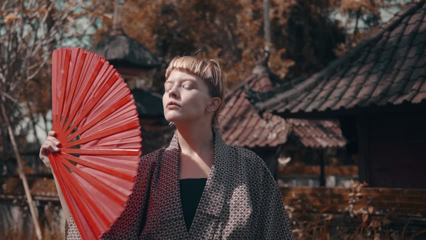 Beautiful fashion girl in kimono with red hand fan posing outdoor near traditional Balinese temple. Portrait of stylish hipster female outdoor | Shutterstock HD Video #1013600354