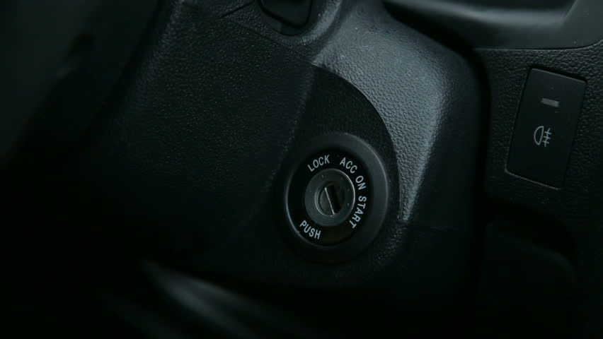 Close-up of the girl turns the ignition key in the car.