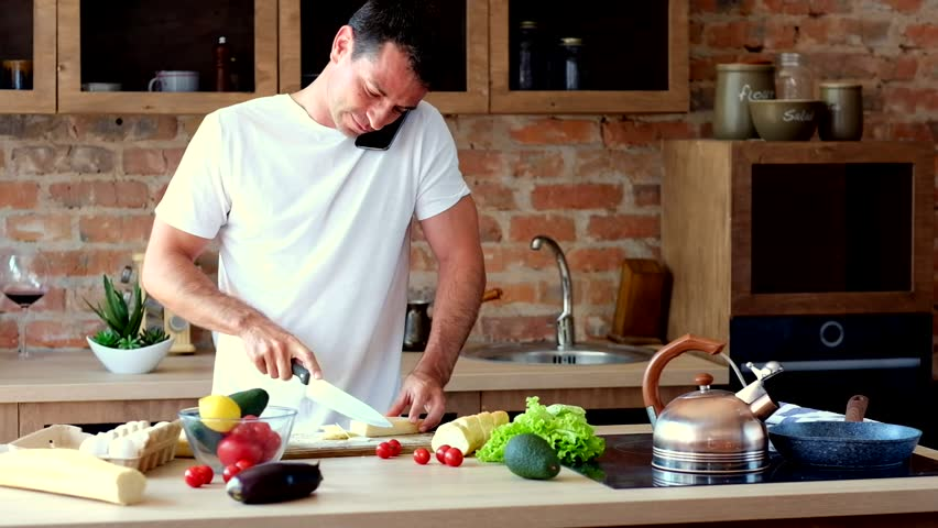 Young attractive man cutting cheese and talking on the phone in the kitchen | Shutterstock HD Video #1013603834