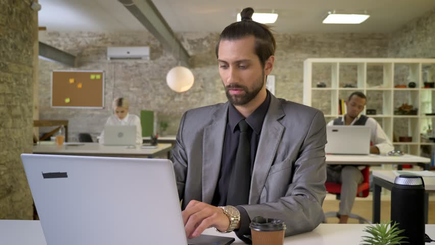 Handsome businesswoman with beard is typing on laptop in office, drinking coffee, colleagues are networking with technologies, work concept, communication concept | Shutterstock HD Video #1013617124