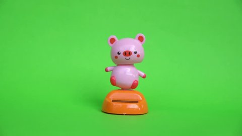 Pink pig doll dancing on green screen background.