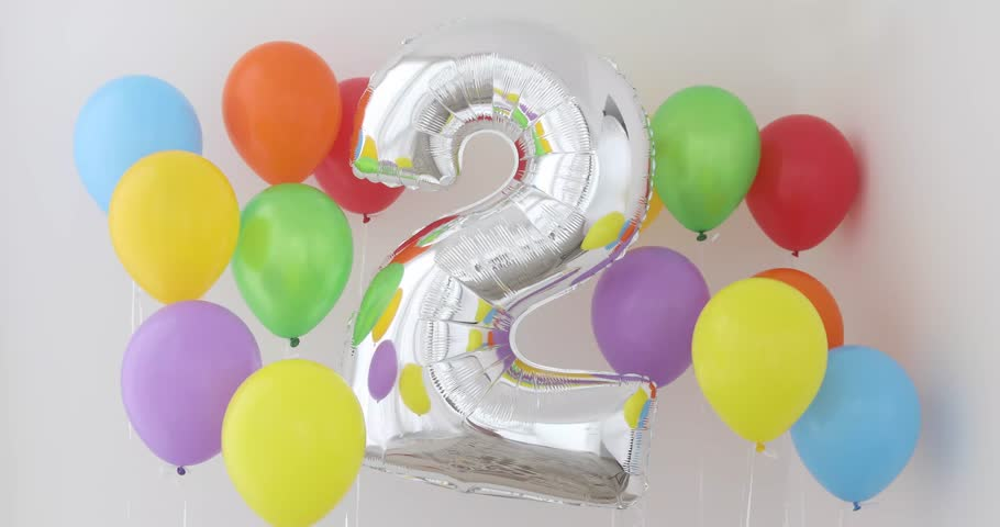 Number 2 (two) of color balloon on a light background. Birthday balloon for baby with , rainbow color- red, orange, yellow, green, sky blue and fiolet balloons | Shutterstock HD Video #1013625314