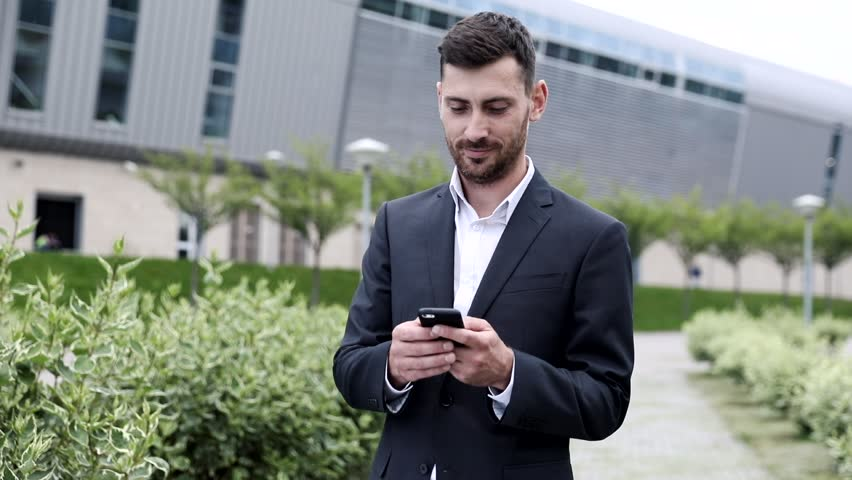 Close up of Handsome Young Businessman Standing in the Park. Working on his Mobile Phone.  | Shutterstock HD Video #1013630774