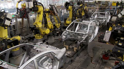 Robotic line at the automobile plant. Robot manipulators collect and weld car bodies