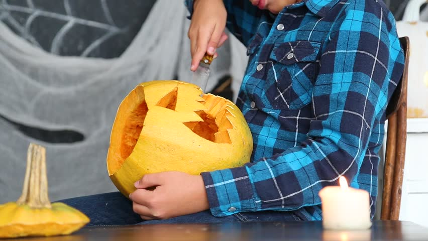 Young boy cutting scary face in pumpkin for Halloween celebration.