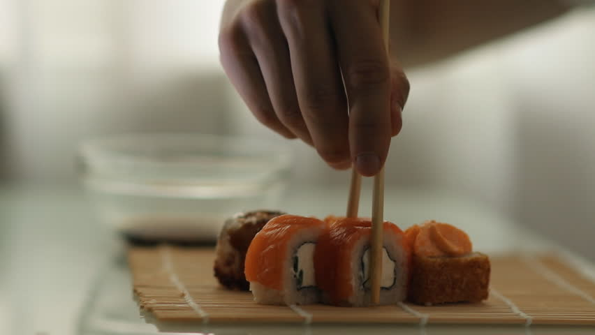 Lunch at a Japanese restaurant. Man eating sushi. | Shutterstock HD Video #1013635604