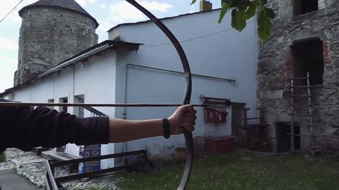 Close up shot of archer with strong hands bending mechanic bow arrow concentrating on target