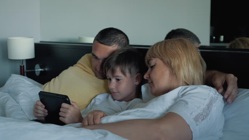 A happy family with one child lying on the bed and using a digital tablet and smartphones. Modern technologies of virtual life | Shutterstock HD Video #1013679164