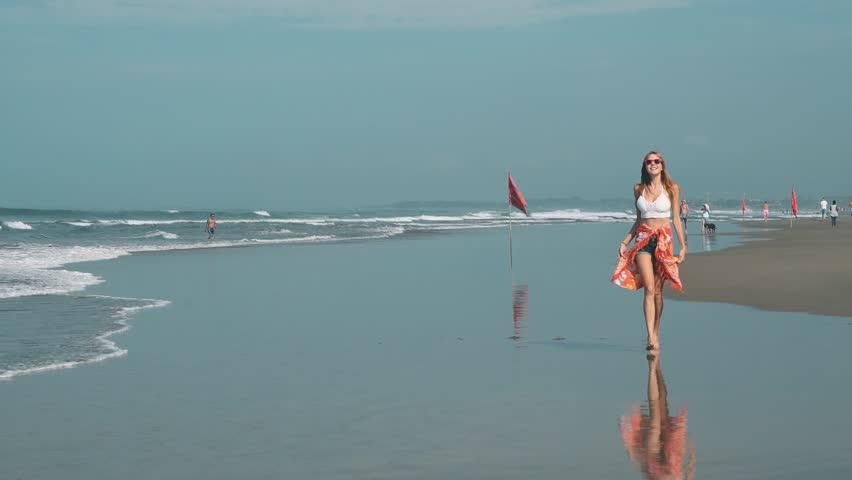 Young woman walking on beach in Seminyak, Bali