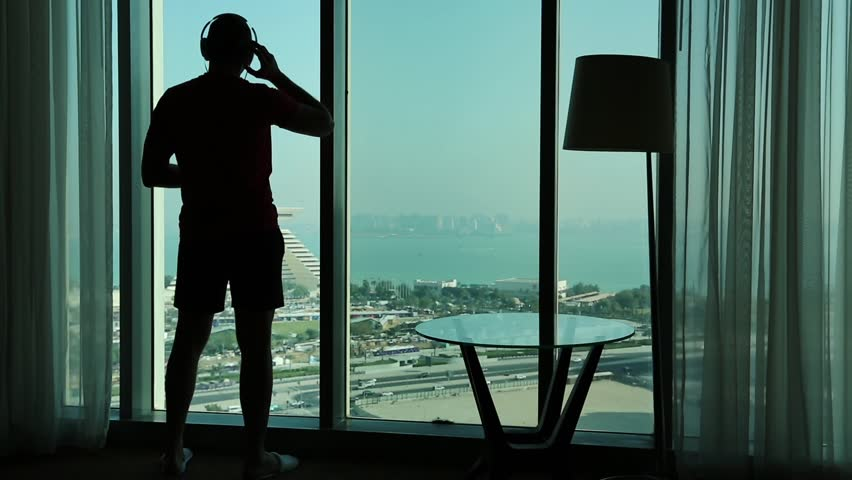 Man listens to music near big window in hotel room. View of coast of the Persian Gulf in Doha city, Qatar, Arabian Peninsula, Middle East #1013681384