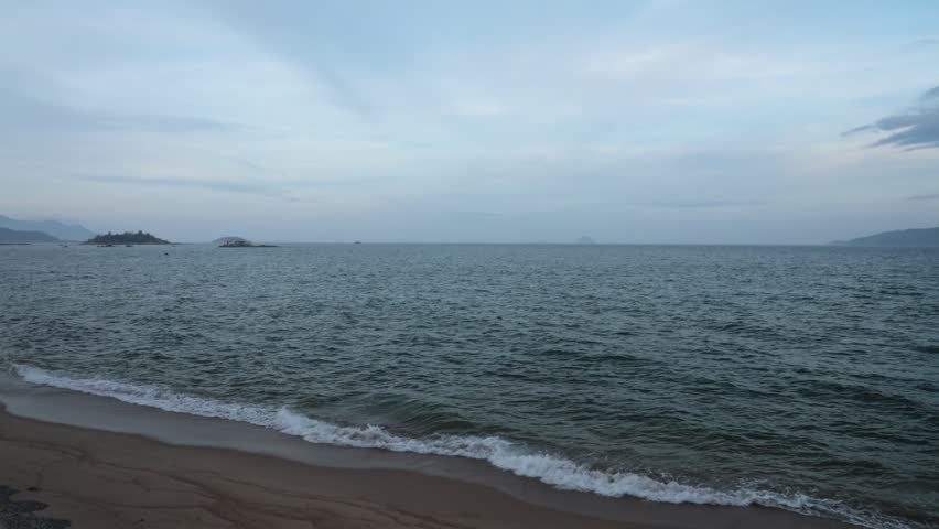 Panning coastline scene with islands on the horizon and cloudy skies looking out over the south china sea in vietnam, high definitionie clip stock footage. Panoramic.