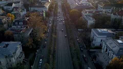 Arial shot flying down a busy Budapest street with sun-flares and vibrant Autumn colors featuring mid century architecture.