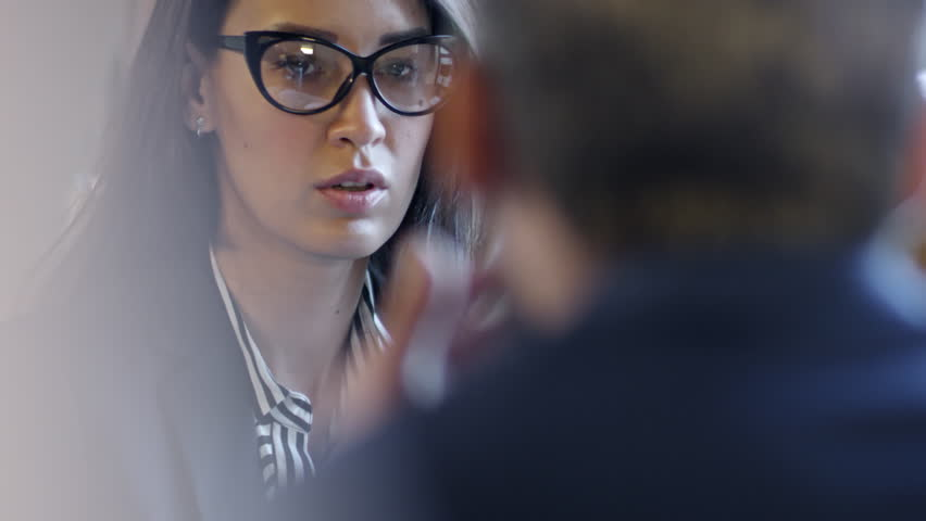Face of serious young businesswoman in glasses listening to unrecognizable colleague seen from their back when discussing agreement details at business lunch | Shutterstock HD Video #1013701334