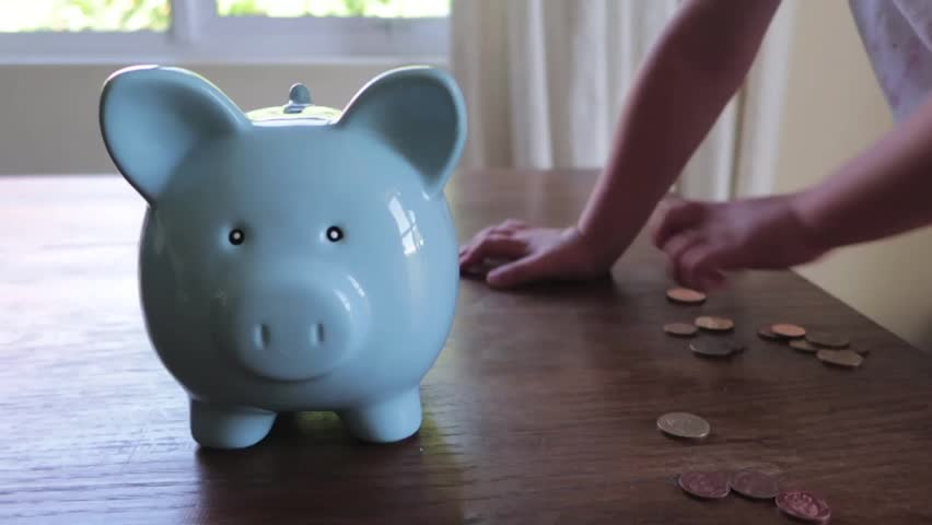 Close up footage of a youg childs hand putting money into a blue piggy bank   Shutterstock HD Video #1013704724