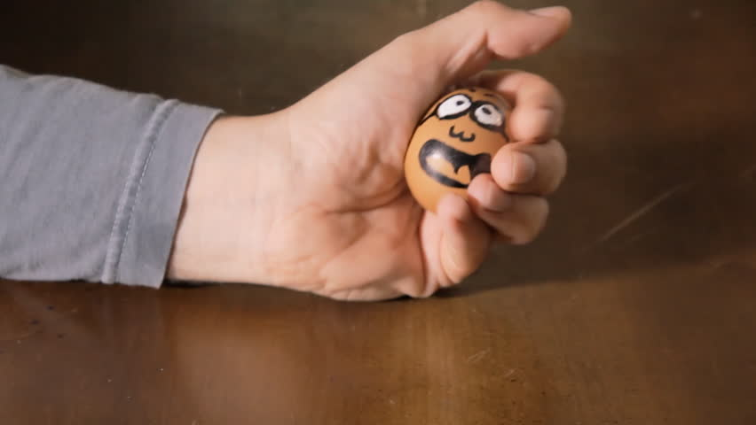 A hand crushing an egg with a drawn horrified face, killing it. Symbolic horror Halloween shot, black humor, dark comedy.  | Shutterstock HD Video #1013705114