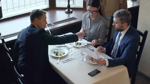 High angle view of three colleagues in formalwear discussing agreement when having business lunch