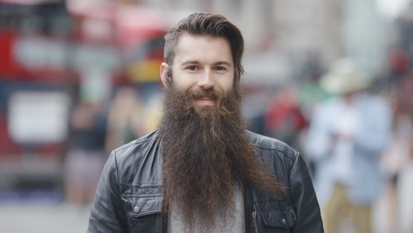 Portrait of a young man with a long beard smiling to camera, in slow motion #1013709614