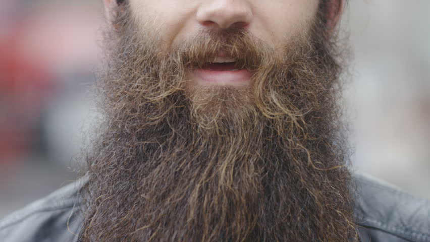 Close up of a man's mouth with a bushy big beard talking to camera