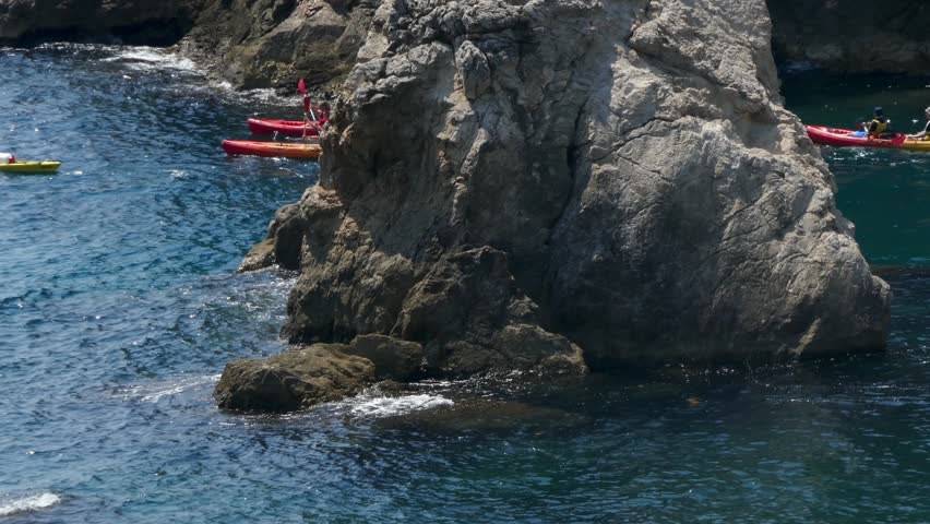 Long shot aerial footage of a group of sea kayakers in an open sea near rock cliffs