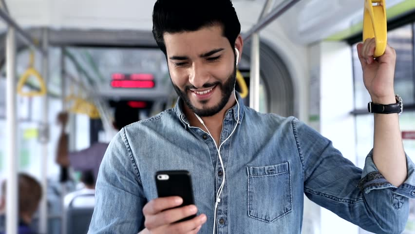 Attractive Bearded Man Standing in the Crowded Tram. Holds the Handrail, Listens to the Music. Man in Public Transport. Using his Smartphone. Stylish Outfit. Modern Wristwatch.   Shutterstock HD Video #1013754584