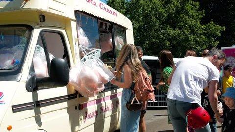 Glasgow, Scotland / United Kingdom (UK) - 06 24 2018: Glasgow, UK, June 2018 - Parents buying ice cream from ice cream van for kids at Glasgow Mela 2018