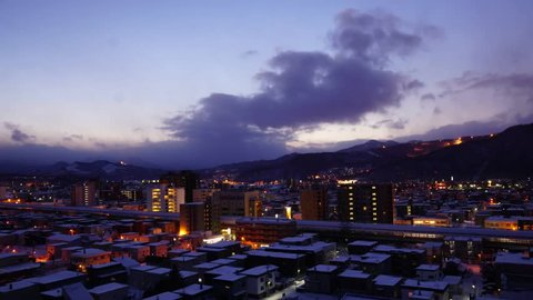 Sunset timelapse of small city in Sapporo with trains and cars