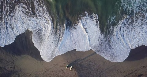 Aerial top view waves break on white sand beach at sunset. Sea waves on the beautiful beach aerial view drone 4k shot. Bird's eye view of ocean waves crashing against an empty beach from above.