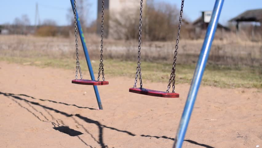 Empty swing swinging in a desolate area. Apocalyptic feel.