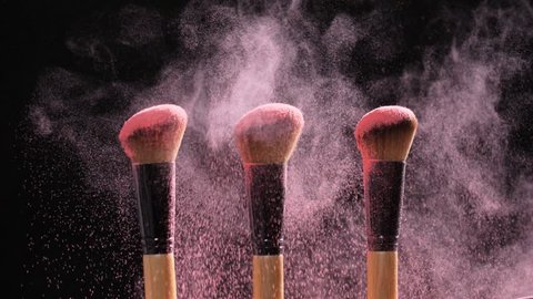 Make-up and beauty concept. Brush with pink powder explosion on black background