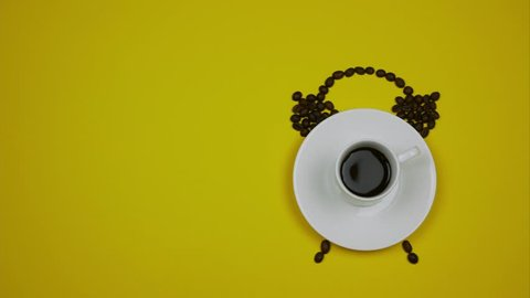 A cup of coffee and coffee beans forming an alarm clock on the yellow background.