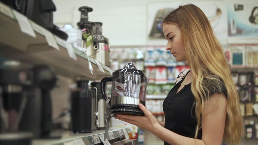 Cute blonde woman holding a brand new juicer for kitchen. Female customer wants to buy juicer to drink fresh juice at home. | Shutterstock HD Video #1013807504