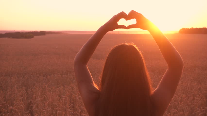 Silhouette of young girl standing at wheat field making heart symbol with his hands at sunset