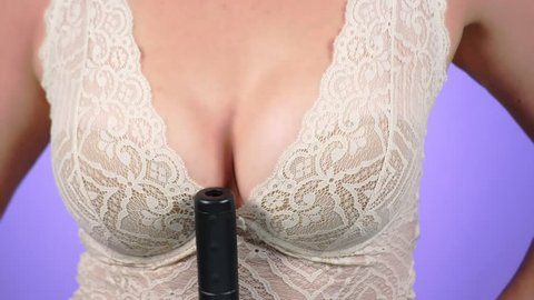 4k. Close-up. Slow motion. A woman with a big breast holds a gun