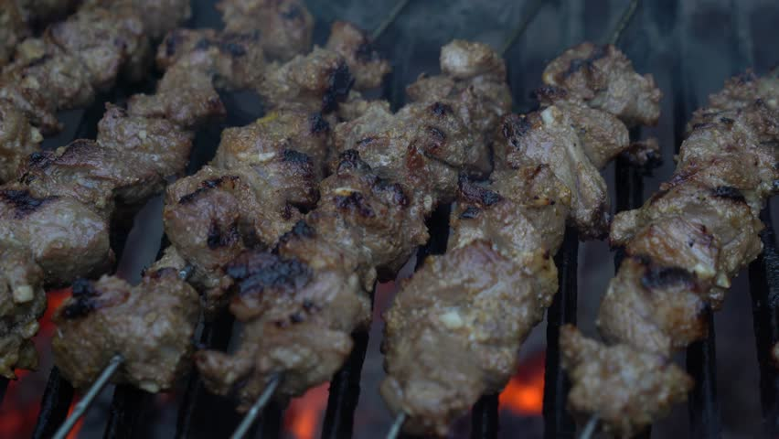 Closeup sliding to the left of charred lamb skewers of shish kabob on a smoking hot grill.
