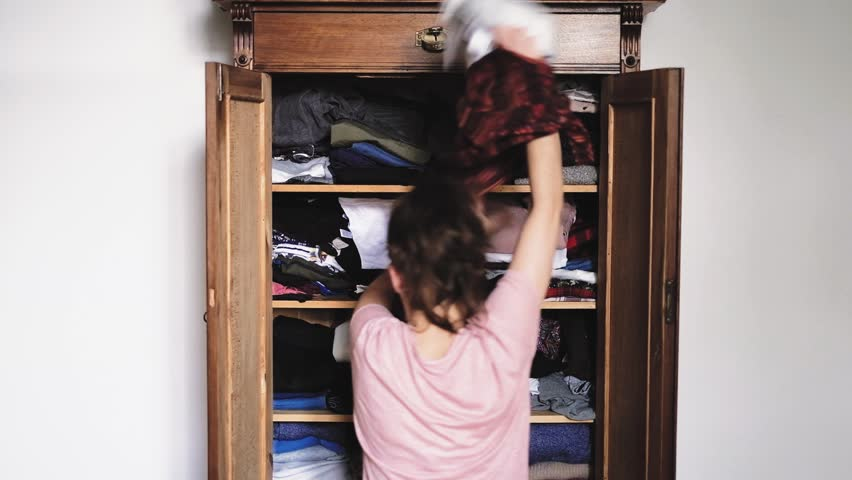 Angry young woman is throwing clothes from old retro vintage wooden wardrobe and after unsuccessful clothes search, view from back, slow motion 1920p HD