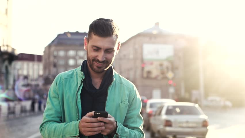 Handsome Bearded Man Walking in the Wide Street. Holding Modern Mobile Phone in his Hands. Man Walking in the Crowded Street full of Cars. Big Buildings in the City Centre. | Shutterstock HD Video #1013876834