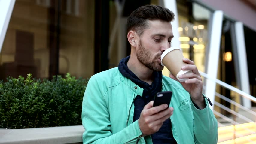 Happily Smiling Attractive Man Standing by the Modern Building's Entrance. Drinking Tasty Coffee. Typing a Message on his Phone. Using Modern App. Pleasant Mood. City Center. | Shutterstock HD Video #1013876864