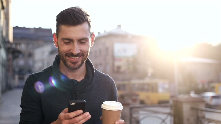 Attractive Bearded Man Walking on the Pavement in the Big Town. Typing a Message on his Mobile Phone. Drinking Tasty Coffee. Modern and Classical Buildings on the Background. | Shutterstock HD Video #1013876894