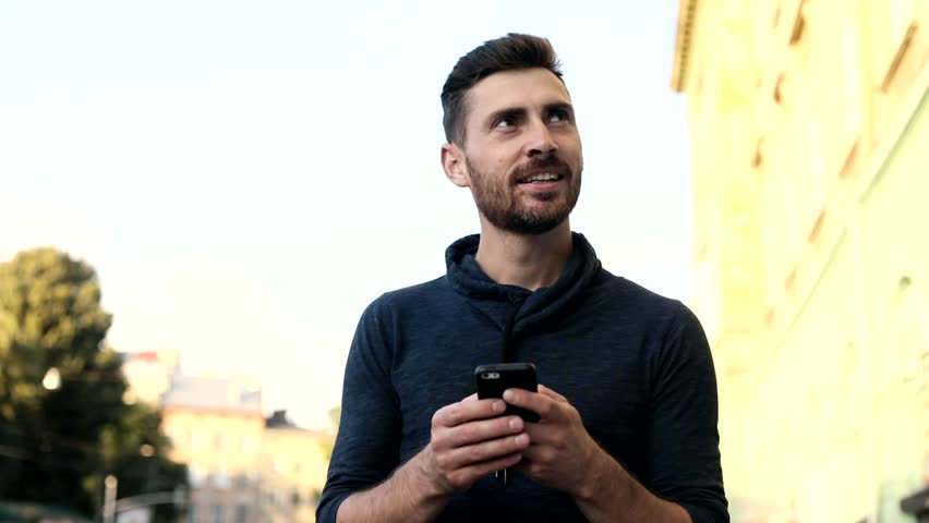 Close up view of Handsome Young Man in the Big Town. Bearded Man Using his Mobile Phone. Casually Dressed. Pleasant Mood. Happily Smiling Man. Big Buildings on the Background. | Shutterstock HD Video #1013880374