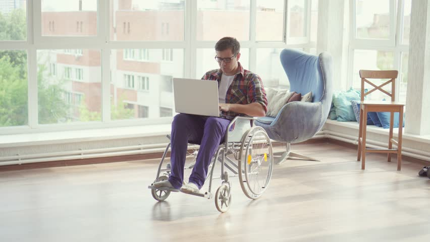 Disabled man in wheelchair with laptop in his apartment.