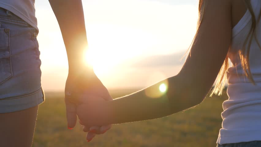 Mother and daughter walking and holding hands in the meadow at sunset. Close up shot of mother hands taking the hands of daughter at golden field on the sunset background. #1013890214