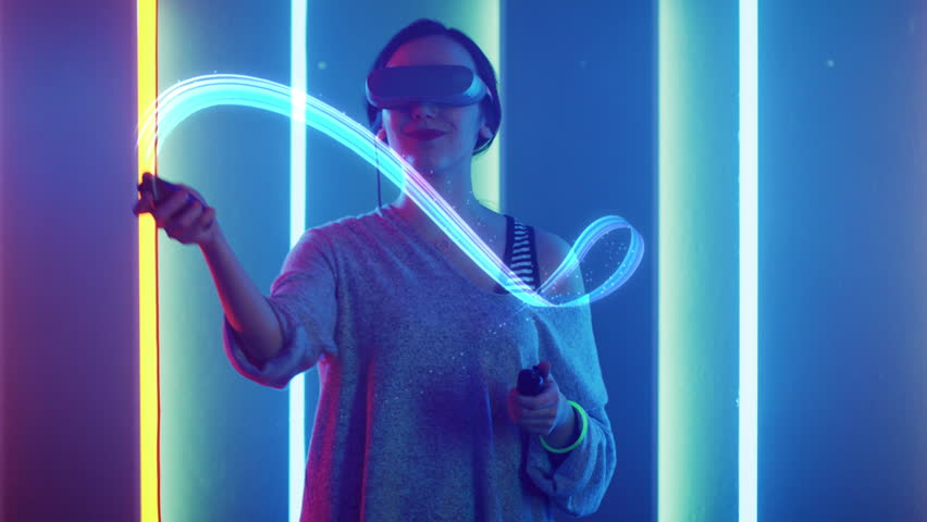 Beautiful Young Girl Wearing Virtual Reality Headset Draws Abstract Lines and Figures with Joysticks / Controllers. Creative Young Girl Does Concept Art with Augmented Reality. Shot on 4K UHD.