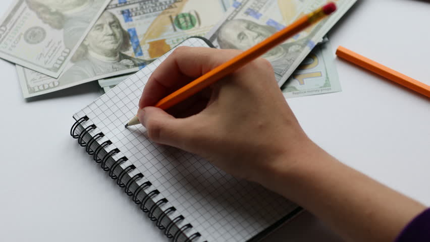 Calculating and taking notes in notebook, on working desk, money | Shutterstock HD Video #1013925884