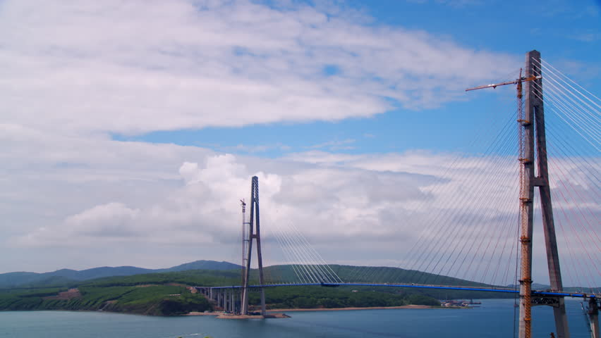 Construction of a huge bridge in the Russky Island, Russia. Beautiful picture of the bridge, sea, forest, blue sky and clouds around  | Shutterstock HD Video #1013953604