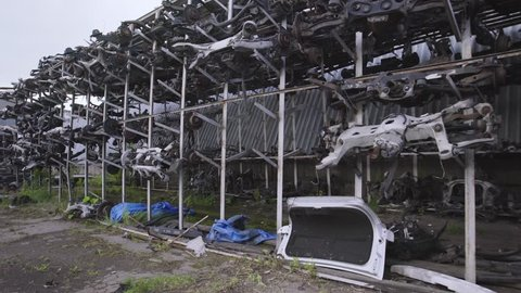 Racks with many different spare parts: beams of automobile suspension, steering racks, automobile suspension, shock absorbers, stabilizers assembled. Used cars junkyard.