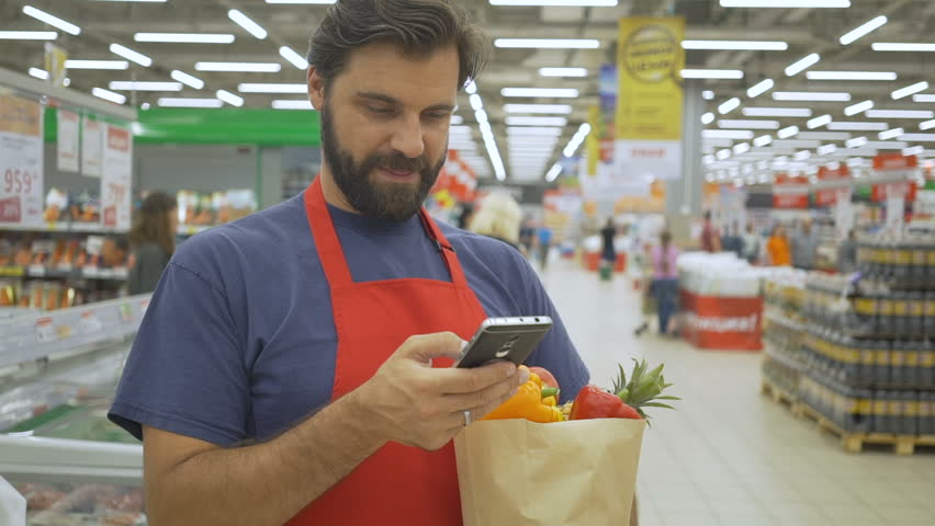 Smiling supermarket employee using mobile phone and holding shopping bag in supermarket | Shutterstock HD Video #1013987474